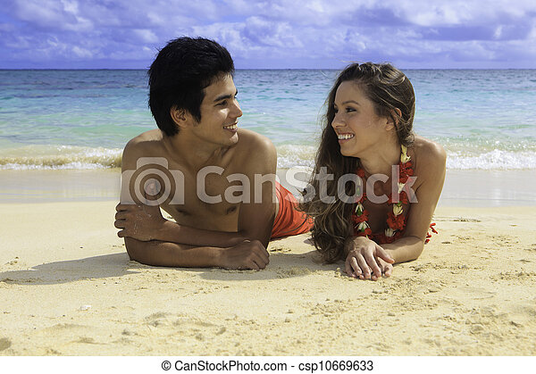 couple lounging on a hawaii beach - csp10669633