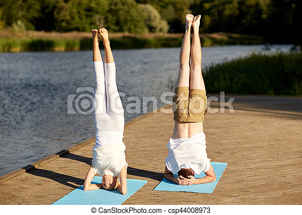 couple making yoga headstand on mat outdoors fitness