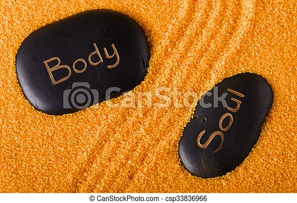 Couple of black stones in yellow sand - csp33836966