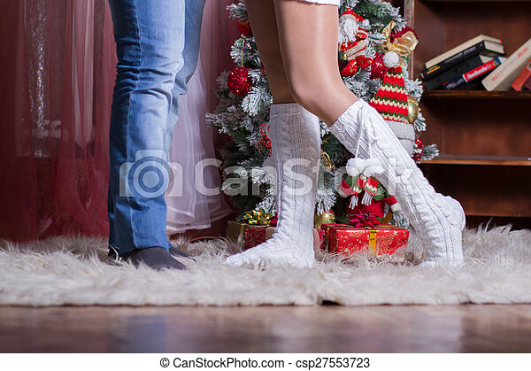 couple of male and female legs on the background Christmas Interior - csp27553723