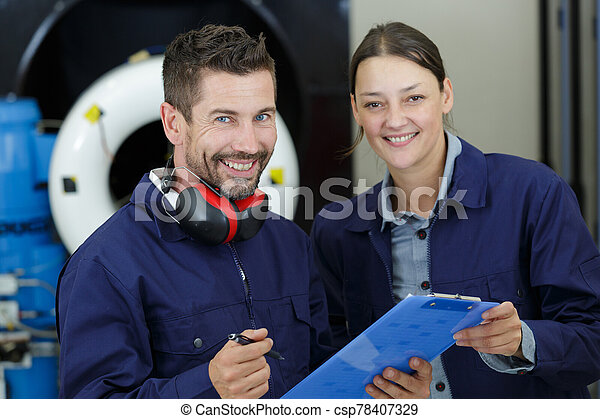 couple of positive work people laughing at the camera - csp78407329