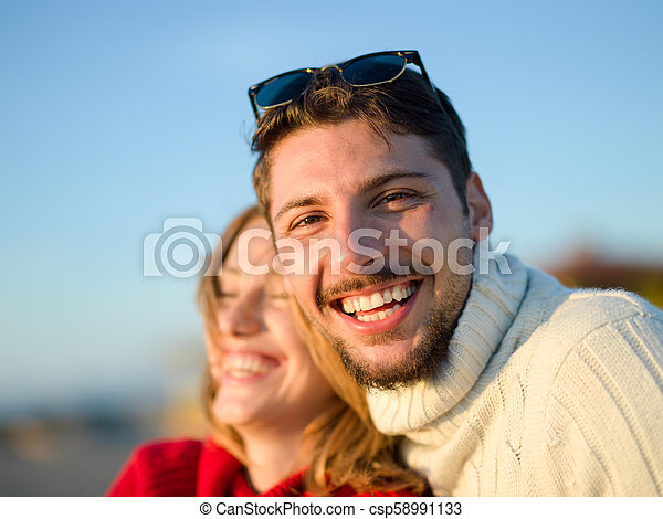 couple on a beach at autumn sunny day - csp58991133