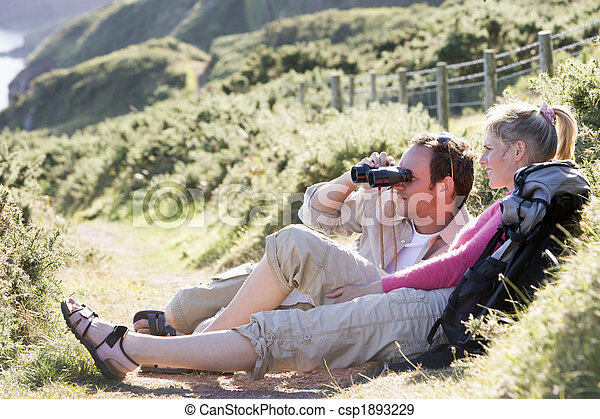 Couple on cliffside outdoors using binoculars and smiling - csp1893229
