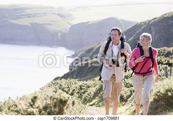 Couple on cliffside outdoors walking and smiling - csp1709881
