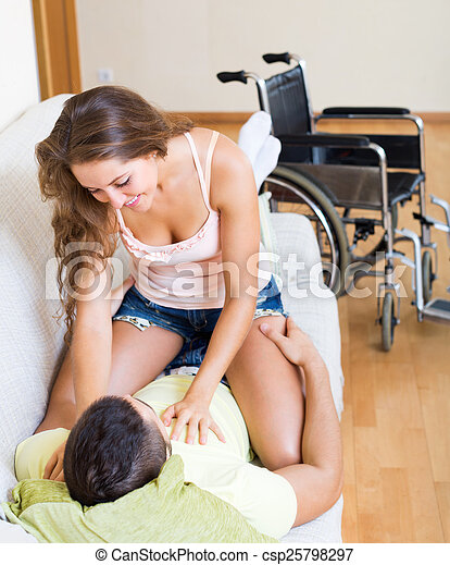 Couple on couch near wheelchair - csp25798297
