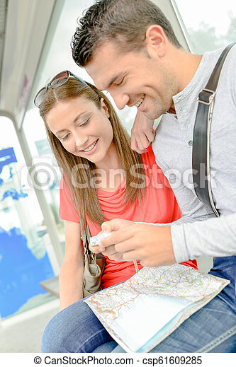 Couple on public transport, looking at photos on digital camera - csp61609285
