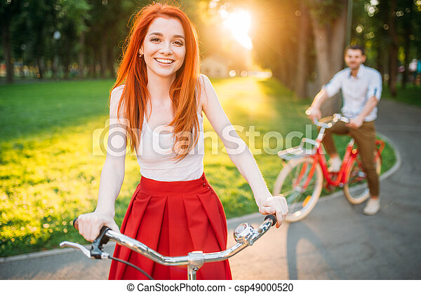Couple on retro bicycles on sunset, romantic date - csp49000520