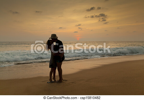 couple on the beach with romantic sunset - csp15810482