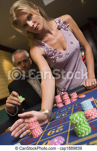 Couple placing bet at roulette table - csp1889839