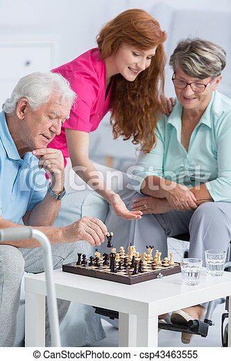 Couple playing chess in nursing home - csp43463555