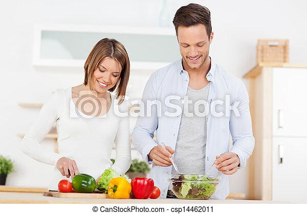 Couple preparing salad in the kitchen - csp14462011
