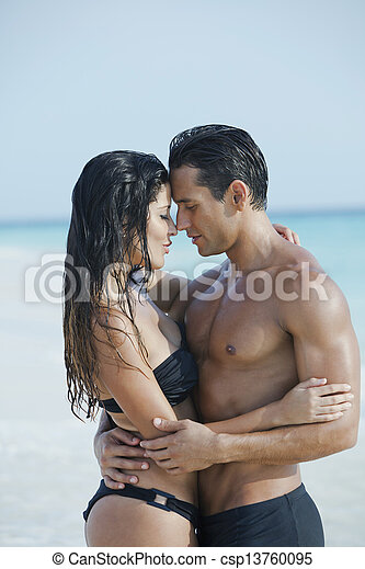 couple romancing on the beach day time