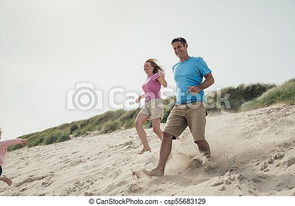 Couple Running Down a Sand Dune - csp55683129