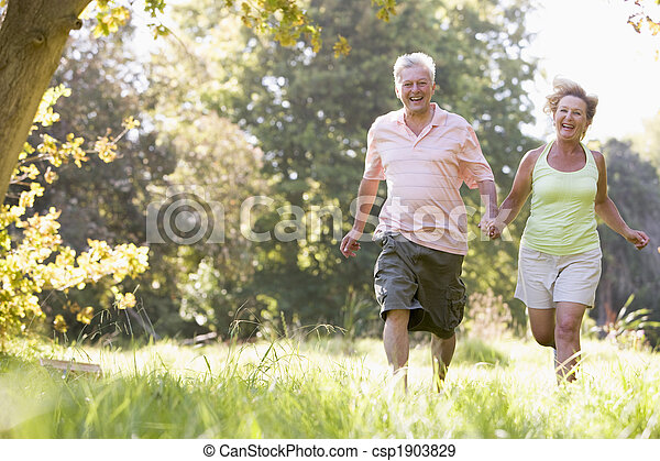 Couple running in park holding hands and smiling - csp1903829