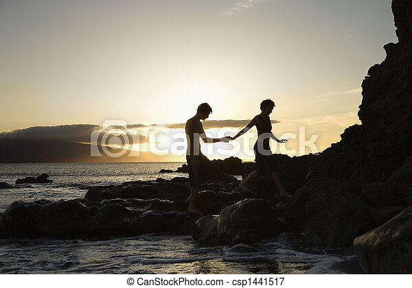 Couple silhouetted on beach. - csp1441517