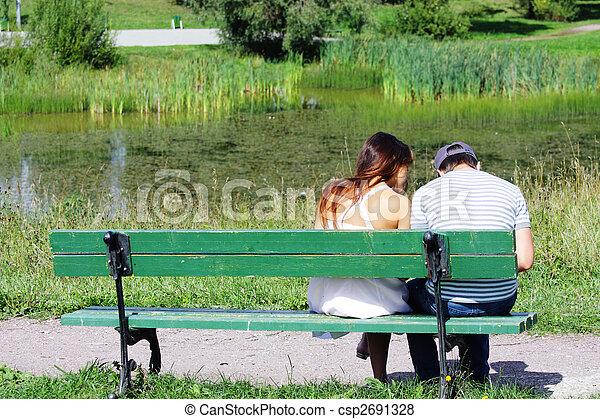 Couple sitting at pond - csp2691328