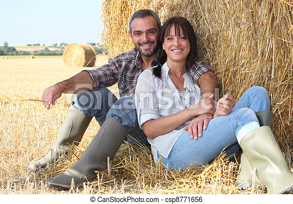 Couple sitting in front of haystack - csp8771656