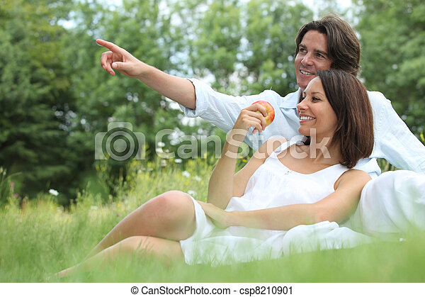 Couple sitting in the grass - csp8210901
