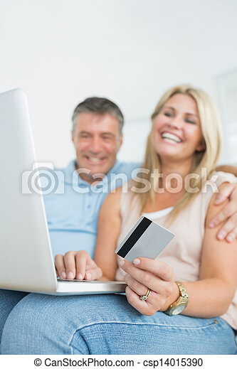 Couple sitting on sofa shopping online - csp14015390