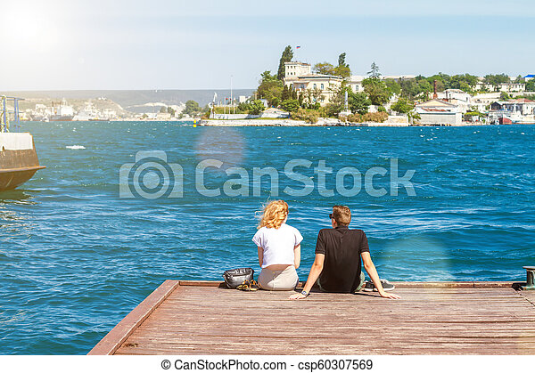 couple sitting on the pier on a Sunny day - csp60307569