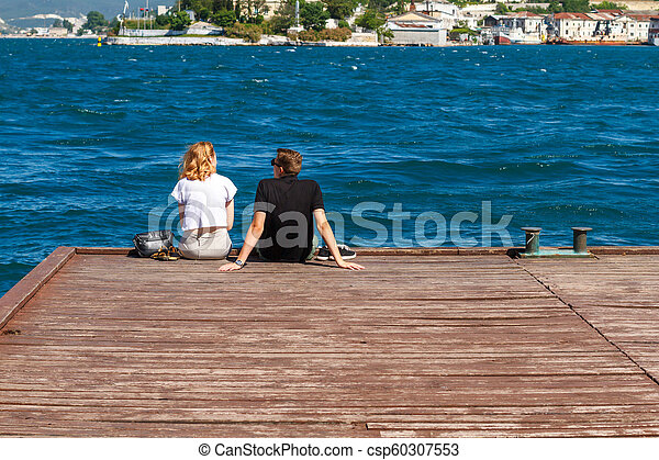 couple sitting on the pier on a Sunny day - csp60307553