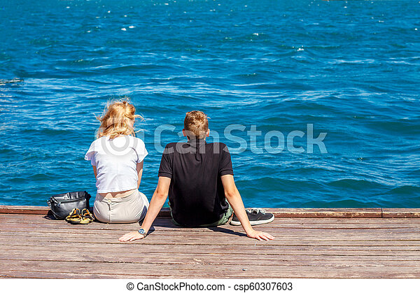 couple sitting on the pier on a Sunny day - csp60307603