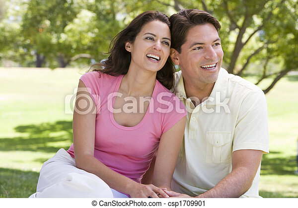Couple sitting outdoors smiling - csp1709901