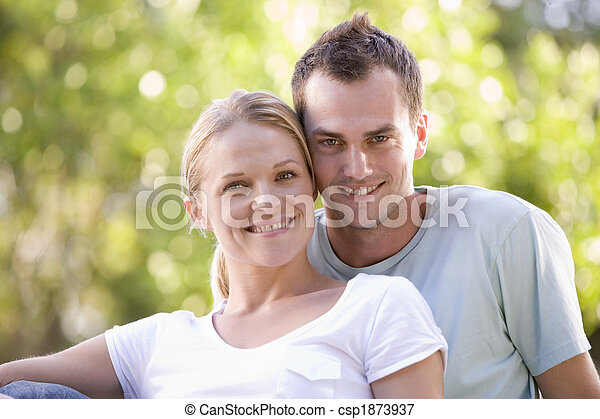 Couple sitting outdoors smiling - csp1873937