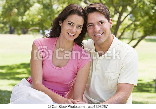 Couple sitting outdoors smiling - csp1893267