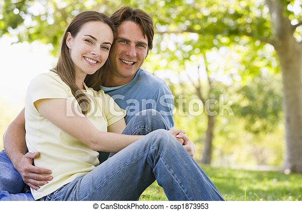 Couple sitting outdoors smiling - csp1873953