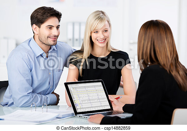 Couple Smiling While Looking At Financial Advisor At Desk - csp14882859