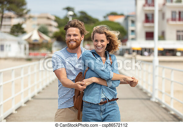 couple standing on beach pier embracing - csp86572112
