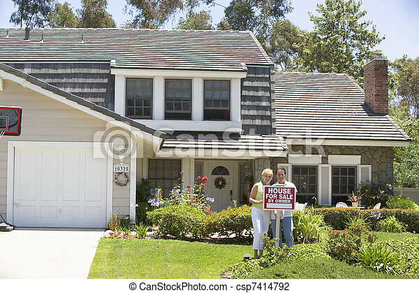 Couple Standing Outside House With Real Estate Sign - csp7414792
