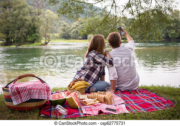 Couple taking a selfie by mobile phone while enjoying picnic time - csp62775731