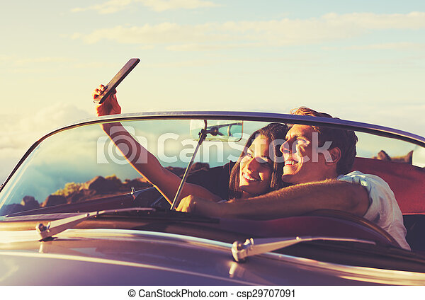 Couple Taking a Selfie in Car at Sunset - csp29707091