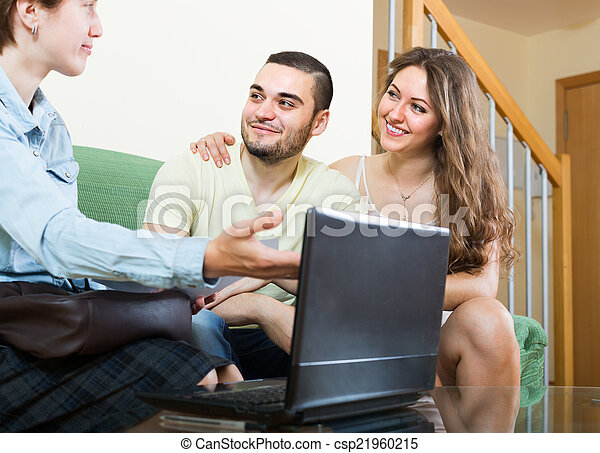 Couple talking with social worker at home - csp21960215