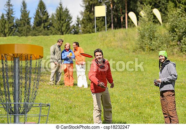 Couple throwing frisbee disc at springtime park - csp18232247