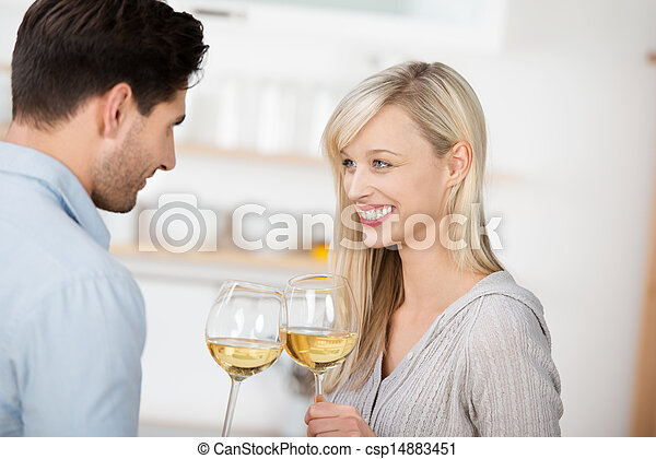 Couple Toasting Wine Glasses In Kitchen - csp14883451