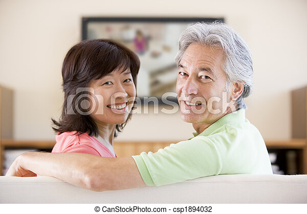 Couple watching television smiling - csp1894032