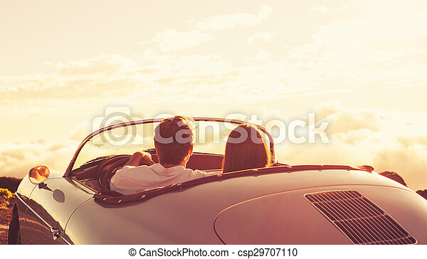 Couple Watching the Sunset in Classic Vintage Car - csp29707110
