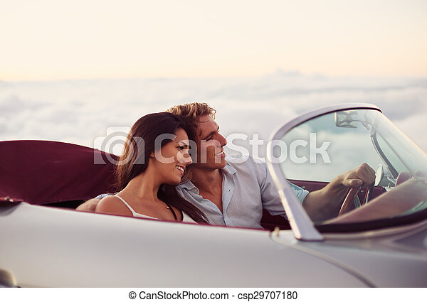 Couple Watching the Sunset in Classic Vintage Car - csp29707180