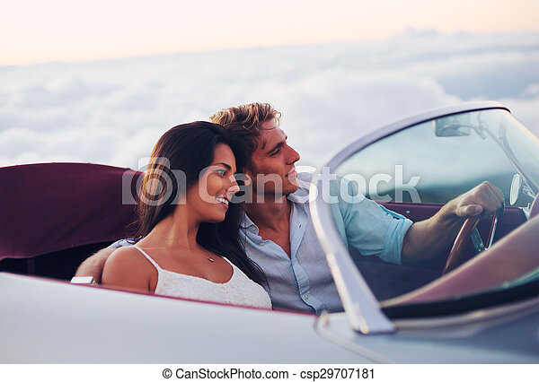 Couple Watching the Sunset in Classic Vintage Car - csp29707181