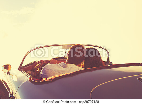 Couple Watching the Sunset in Classic Vintage Car - csp29707128