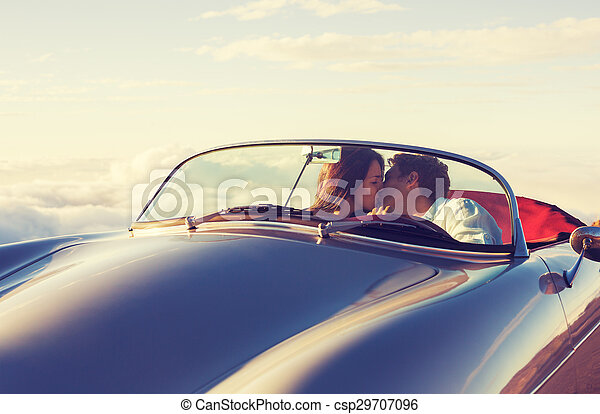 Couple Watching the Sunset in Classic Vintage Car - csp29707096