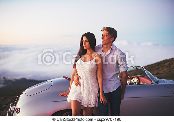 Couple Watching the Sunset with Classic Vintage Car - csp29707190