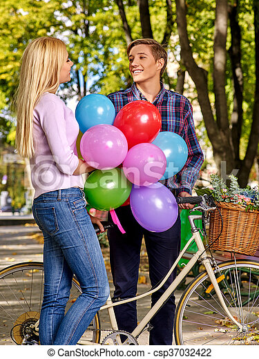 Couple with balloons on retro bike in park. - csp37032422