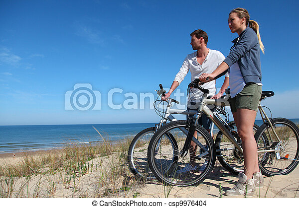 Couple with bicycles looking at the ocean - csp9976404
