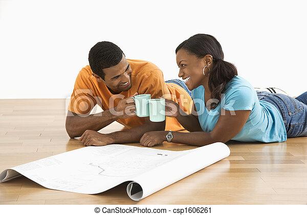 Couple with blueprints toasting. - csp1606261