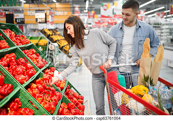 Couple With Cart Choosing Peppers In Supermarket