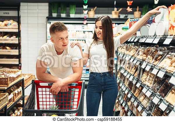 Couple With Cart Choosing Products In Supermarket